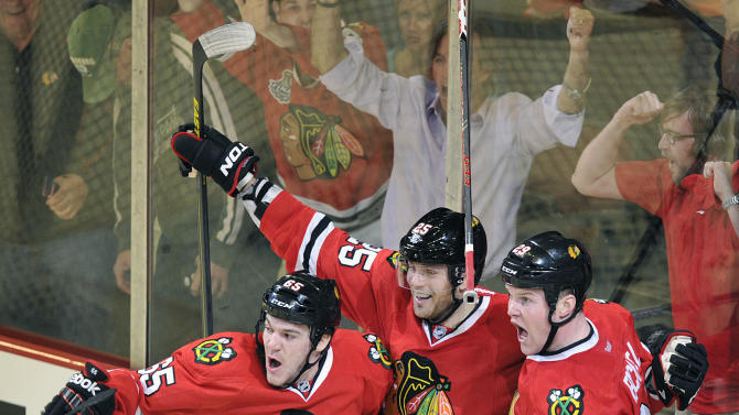 Chicago Blackhawks' Andrew Shaw left, Viktor Stalberg and Bryan Bickell (29) celebrate Bickell's game winning goal against the Minnesota Wild in overtime of Game 1 of an NHL hockey Stanley Cup playoff series Tuesday, April 30, 2013, in Chicago. The Blackhawks defeated the Wild 2-1. (AP Photo/Jim Prisching)