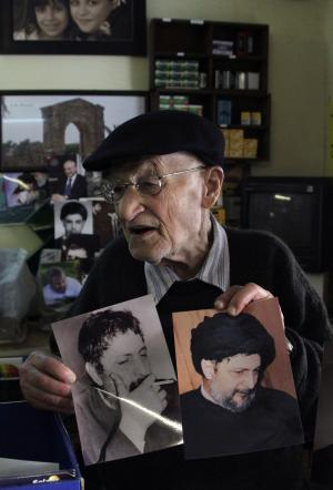 In this Feb. 23, 2011 photo, Lebanese photographer Mohammed Turjuman, shows portraits he took of Shiite cleric Imam Moussa al-Sadr who went missing with his two companions during an official visit to Libya in 1978, in his studio in the southern port city of Tyre, Lebanon. More than three decades after he disappeared while on a trip to Libya, the fate of al-Sadr, still evokes fresh anger and strong emotions among his supporters. Many in Lebanon are hoping that as Moammar Gadhafi's 42-year-old grip on power weakens, the fate of the missing imam will finally be revealed. (AP Photo/Mohammed Zaatari)