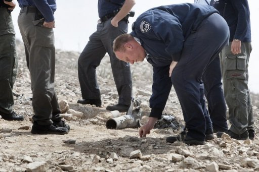 Israeli police inspect the remains of a Grad rocket fired by Palestinian militants into the southern Israeli city of Beersheva in March 2011