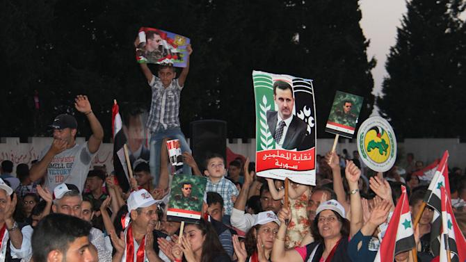 In this Saturday, May 31, 2014, photo released by the Syrian official news agency SANA, supporters of Syrian President Bashar Assad hold his portraits and wave Syrian flags during a demonstration in support of his candidacy for presidential election in the costal city of Tartous, Syria. It is Syria's first multi-candidate presidential election in nearly half a century. But the vote on Tuesday, June 3, still has the feel of a referendum and is being touted by Assad's government as a measuring scale for Syrians' support of his three-year brutal military crackdown on dissent. (AP Photo/SANA)
