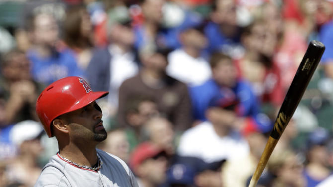 Los Angeles Angels' Albert Pujols (5) watches the flight of his two-run home run off of Texas Rangers' Matt Harrison in the first inning of a baseball game Saturday, April 6, 2013, in Arlington, Texas. The shot scored Erick Aybar. (AP Photo/Tony Gutierrez)