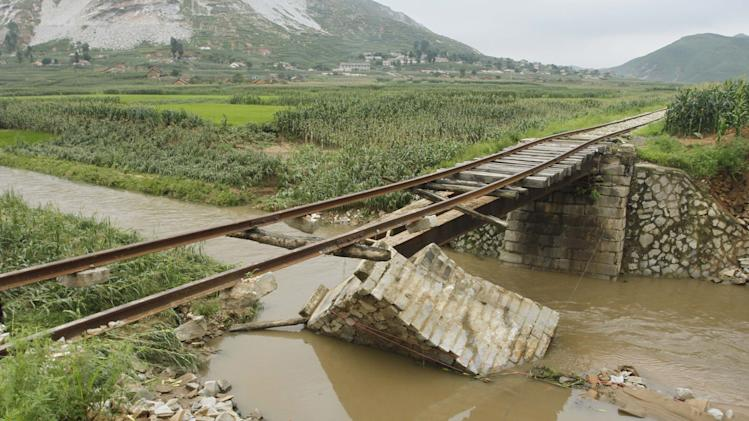 In this July 30, 2012 photo, a bridge supporting railway lines is destroyed after heavy rain in Onchon County, North Korea. The rain Sunday and Monday followed downpours earlier this month that killed nearly 90 people and left more than 60,000 homeless, officials said. The floods also come on the heels of a severe drought, fueling renewed food worries about a country that already struggles to feed its people.(AP Photo/Jon Chol Jin)