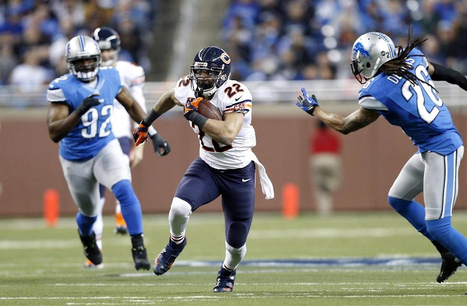 Chicago Bears running back Matt Forte (22) runs between Detroit Lions defensive end Cliff Avril (92) and free safety Louis Delmas (26) during the second quarter of an NFL football game at Ford Field in Detroit, Sunday, Dec. 30, 2012. (AP Photo/Rick Osentoski)