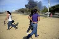 Local residents pass by the Amuay oil refinery, part of the Paraguana Oil Refining Complex, still on fire in Paranagua, Venezuela