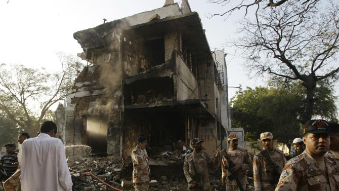 Troops of Pakistan's para-military force stand near the site of an explosion in Karachi, Pakistan on Thursday, Nov. 8, 2012. A suicide bomber smashed a truck packed with explosives into housing for a paramilitary force protecting Pakistan's largest city, killing at least one person in the explosion Thursday morning that sent a large plume of smoke into the sky, officials said. (AP Photo/Fareed Khan)