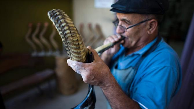 Shimon Keinan blows a shofar in his workshop in Givaat Yoav in the Golan Heights