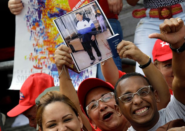 Supporters of Venezuela&#39;s President Hugo Chavez hold up a photo of him at an event commemorating the 1958 fall of the country&#39;s dictatorship in Caracas, Venezuela, Wednesday, Jan. 23, 2013. Chavez, who was re-elected to another six-year term in October, has not appeared or spoken publicly since he left for Havana on Dec. 10. Government officials have said the 58-year-old president is improving after suffering complications including a severe respiratory infection, but they have not provided specific details about his health. (AP Photo/Fernando Llano)