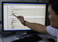 CORRECTS MAGNITUDE - Philippine Institute of Volcanology and Seismology (PHIVOLCS) staff points to the digital seismograph of the magnitude 6.8 earthquake which hit central Philippines on Monday Feb.6, 2012 at suburban Quezon city northeast of Manila, Philippines. Officials said the quake in central Philippines killed at least five people as it destroyed buildings, triggered landslides that buried dozens of houses, trapping residents and listed 29 more as missing. (AP Photo/Bullit Marquez)
