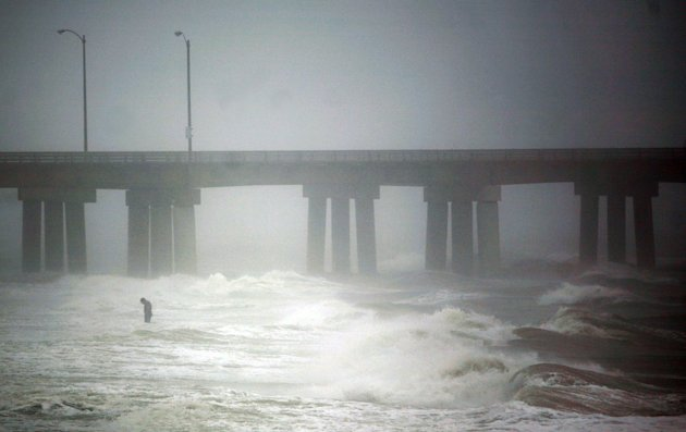 As Hurricane Irene spins north, a lone figure stands in the surf of the Chesapeake Bay near the Chesapeake Bay Bridge Tunnel in Virginia Beach, Va., Saturday, Aug. 27, 2011. (AP Photo/The Virginian-Pi