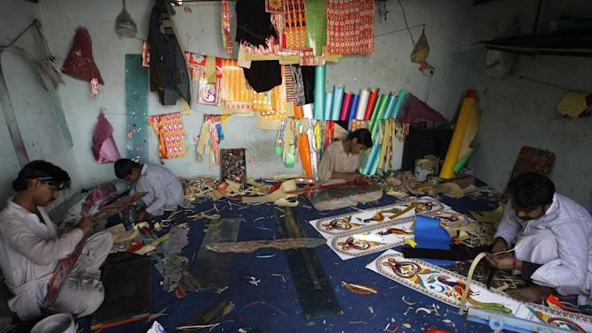 In this Saturday, Feb. 2, 2013 photo, Pakistani artists prepare colorful panels for rickshaws in Karachi, Pakistan. Pakistani youth leader Syed Ali Abbas Zaidi, has an innovative plan to counter the relentless message of violence spewed forth by radical Islamic groups in the country and is stealing a trick from their playbook to do it. His weapon: the three-wheeled motorized rickshaws that buzz along Pakistan's streets carrying paying customers. (AP Photo/Fareed Khan)