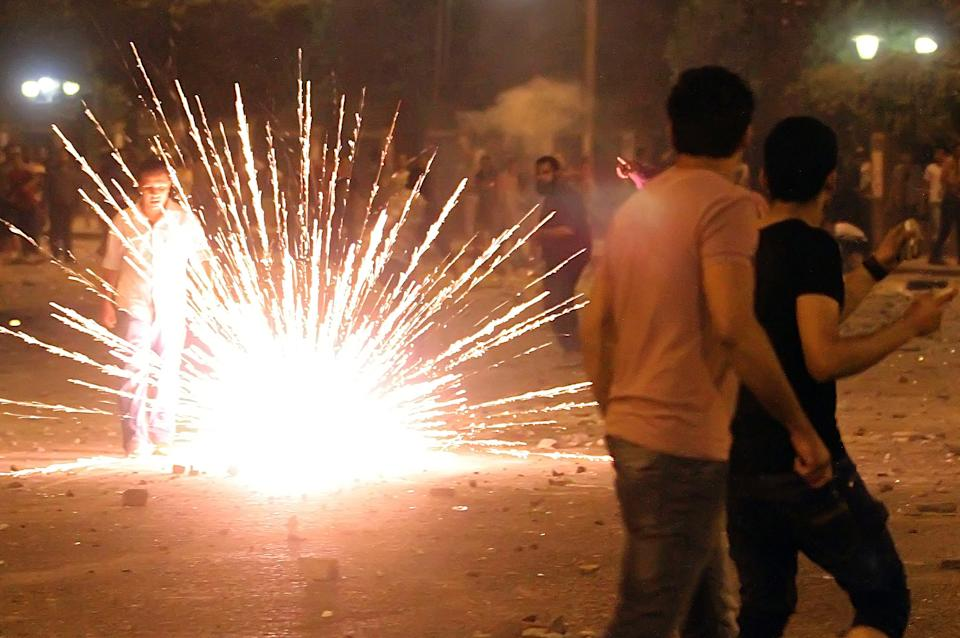 A protester watches fireworks burn during clashes early Sunday, April 29, 2012 in Cairo, Egypt. Security officials say a protester has been killed when clashes erupted between unidentified assailants and demonstrators gathered outside the Defense Ministry in the Egyptian capital to call for an end to military rule. (AP Photo/Ahmed Ali)