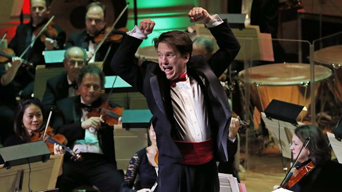 """FILE - In this Dec. 10, 2014 file photo, Boston Pops Conductor Keith Lockhart leads the 31st annual """"A Company Christmas at Pops"""" at Symphony Hall in Boston. Lockhart was just 35 when he took over as conductor of the Pops in 1995. Now in his 20th season, Lockhart has raised his baton 1,700 times to lead the group nicknamed """"America's Orchestra."""" (AP Photo/Elise Amendola, File)"""