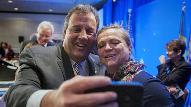 New Jersey Gov. Chris Christie takes a cell phone photo with NGA staffer Lily Kersh during the National Governor's Association Winter Meeting in Washington, Saturday, Feb. 22, 2014. (AP Photo/Cliff Owen)