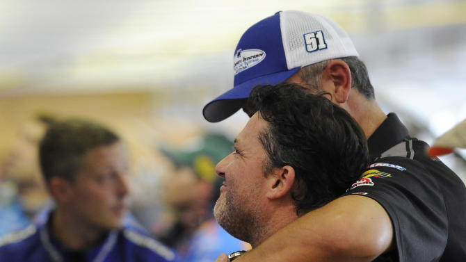 Sprint Cup Series driver Tony Stewart gets a hug from former crew chief Steve Addington in the garage during practice for Sunday's NASCAR Sprint Cup Series auto race at Atlanta Motor Speedway, Saturday, Aug. 30, 2014 in Hampton, Ga. (AP Photo/David Tulis)