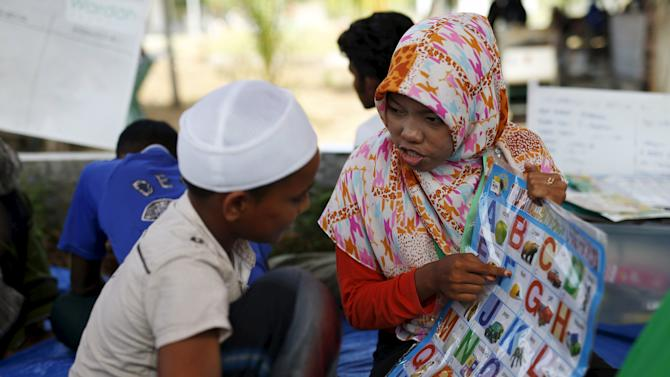 A Rohingya migrant boy, who arrived in Indonesia recently by boat, receives language classes from a volunteer at a temporary shelter in Kuala Langsa