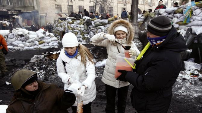 Volunteers distribute borshch to anti-government protesters near a barricade at the site of clashes with riot police in Kiev