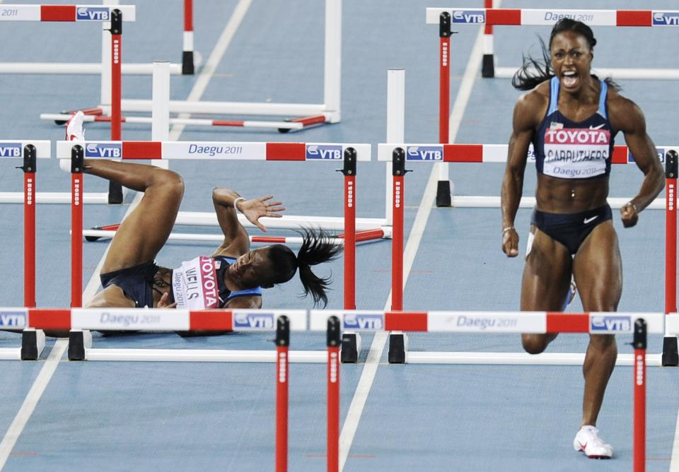 USA's Kellie Wells, left, fails to clear a gate as she competes beside USA's Danielle Carruthers in the Women's 100-meter hurdles final at the World Athletics Championships in Daegu, South Korea, Saturday, Sept. 3, 2011. (AP Photo/Martin Meissner)