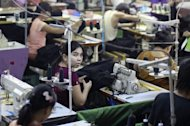 Myanmar labourers work at a garment factory on the outskirts of Yangon in September 2012. Myanmar's parliament on Thursday approved a revised, more business-friendly foreign investment bill aimed at boosting the struggling economy as it emerges from decades of junta rule, lawmakers said