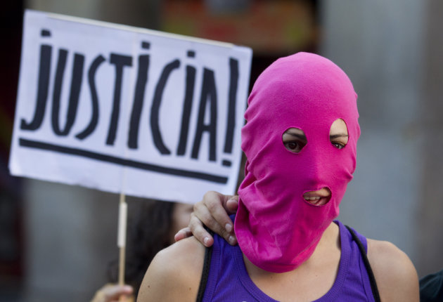 A masked demonstrator stands in front of a placard reading: &#39;Justice&#39; in support of the Russian punk group Pussy Riot during a protest outside Spain&#39;s Foreign Office in Madrid Thursday Aug. 16, 2012. Three members of Pussy Riot were jailed in March and charged with hooliganism motivated by religious hatred after their punk performance against President Putin in Moscows main cathedral. They are awaiting the verdict on Friday, Aug. 17, 2012 (AP Photo/Paul White)
