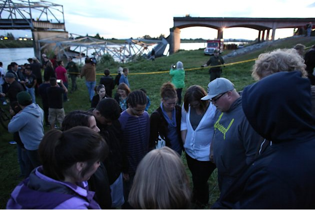 People offer spontaneous prayer after an Interstate 5 bridge collapsed over the Skagit River between Mt. Vernon and Burlington, Wash. on Thursday, May 23, 2013. Two cars and one travel trailer went in