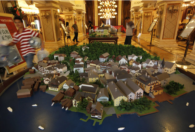 A worker walks past a diorama of an European-style houses in Hallstatt See, a replica of the Austrian town of Hallstatt, in Boluo county, Huizhou city, south China's Guangdong province Saturday, June 