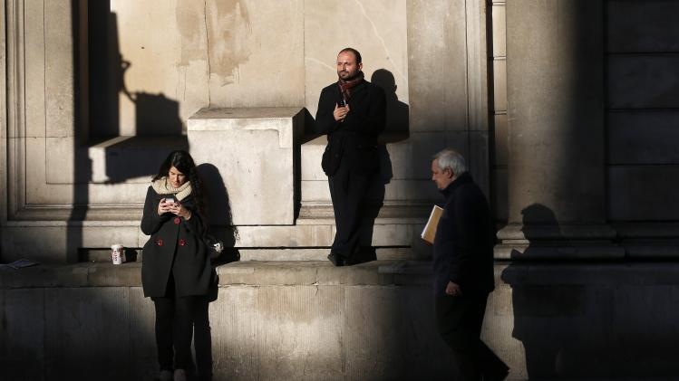 People stand in the sun outside the Bank of England in London