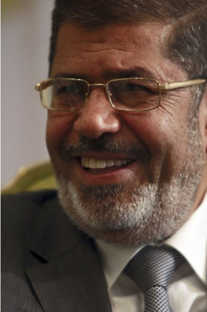Egypt's President Mohamed Mursi smiles during his meeting with Sudan's Foreign Minister Ali Ahmed Karti (not pictured) at the presidential palace in Cairo