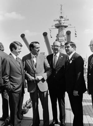 FILE - In this Wednesday, Oct. 7, 1976 file photo, pausing for a picture under the big guns of the decommissioned battleship North Carolina in Wilmington, N.C., is Republican vice presidential candidate Robert Dole, second from left, North Carolina Gov. Jim Holshouser, left, Sen. Jesse Helms, second from right, and on the right is David Flaherty, Republican candidate for governor of North Carolina. Holshouser, who was North Carolina's first Republican governor of the 20th century and then gave early support to Pat McCrory, the first GOP governor of this century, died Monday, June 17, 2013, at age 78. Holshouser had been in declining health before he died at First Health of the Carolinas Medical Center in Pinehurst, his family said in a release through McCrory's office. (AP Photo/Harold Valentine, File)