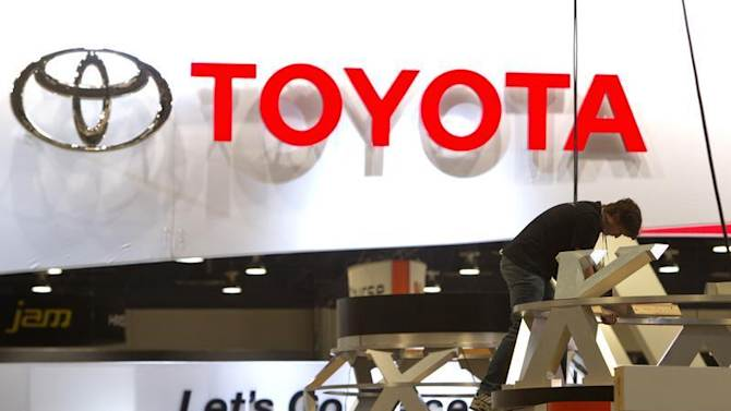 Worker sets up display near Toyota booth in preparation for the 2014 Consumer Electronics Show at the Las Vegas Convention Center in Las Vegas