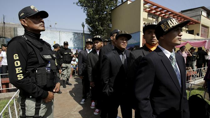 Inmates from Ancon prison next to a security guard prepare to sing at celebrations ahead of Mother's Day at Santa Monica female prison in Lima