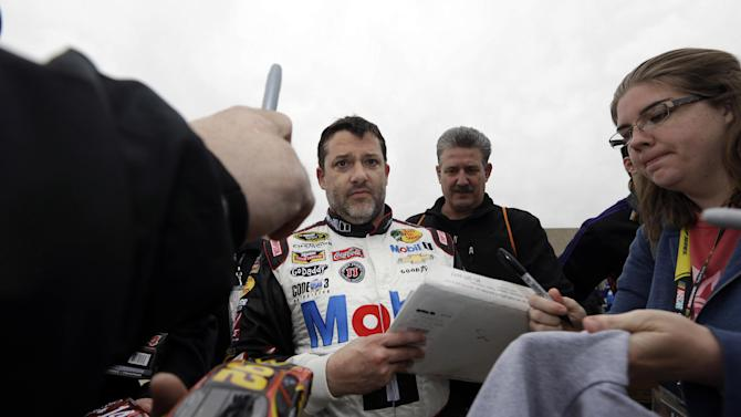 Tony Stewart signs autographs for fans as he walks to his trailer after a practice session for the NASCAR Sprint Cup Series auto race at Texas Motor Speedway in Fort Worth, Texas, Saturday, April 5, 2014