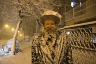 An Ultra-Orthodox Jewish man covered with snow walks in Jerusalem on January 10, 2013. In Jerusalem, at least 10 centimetres of snow blanketed the Holy City by dawn, turning the pine-covered hills into what looked like an Alpine ski resort picture postcard