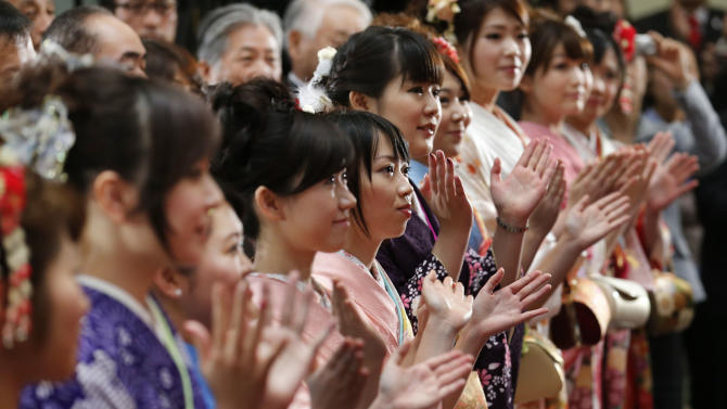 Kimono-clad workers clap their hands in a traditional New Year's opening ceremony at the Tokyo Stock Exchange in Tokyo, Friday, Jan. 4, 2013.  (AP Photo/Koji Sasahara)