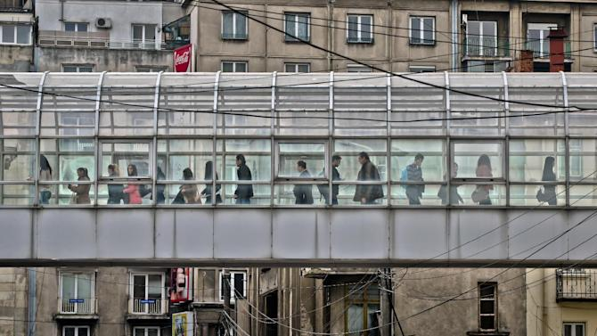 People walk in an overpass connecting two buildings of the Academy of Economic Studies in Bucharest, Romania, Thursday, March 7, 2013.  Romanian President Traian Basescu gestures during an interview with the Associated Press in Bucharest, Romania, Thursday, March 7, 2013.  Romania's president says that the country should do more to tackle corruption if it wants to join the European Union's open border area, known as the Schengen Area. Basescu said that joining the so-called Schengen Area should become a national priority for the country of 19 million which joined the European Union in 2007. The Schengen Area is named after the town in Luxembourg where the open border agreement was signed. (AP Photo/Vadim Ghirda)