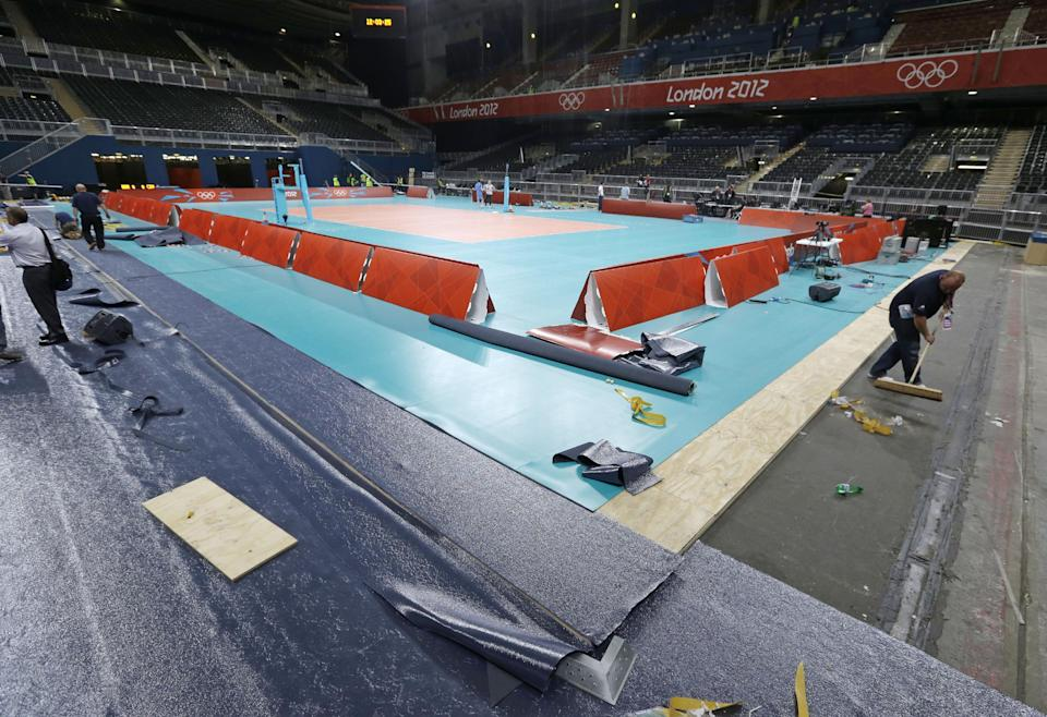 Workers prepare the main volleyball court at Earl's Court, the site of the Volleyball competition, at the 2012 Summer Olympics, Tuesday, July 24, 2012, in London. (AP Photo/Darron Cummings)