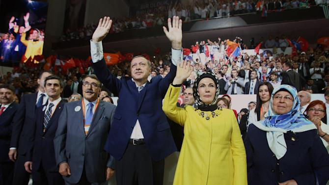 Turkish Prime Minister Recep Tayyip Erdogan and his wife Emine Erdogan salute the members of his ruling Justice and Development Party, AKP, during the congress of AKP in Ankara, Turkey, Sunday, Sept. 30, 2012. Erdogan said Sunday that the era of military coups in the country is over and that Turkey is a model for other Muslim countries to emulate.(AP Photo/Adem Altan, Pool)