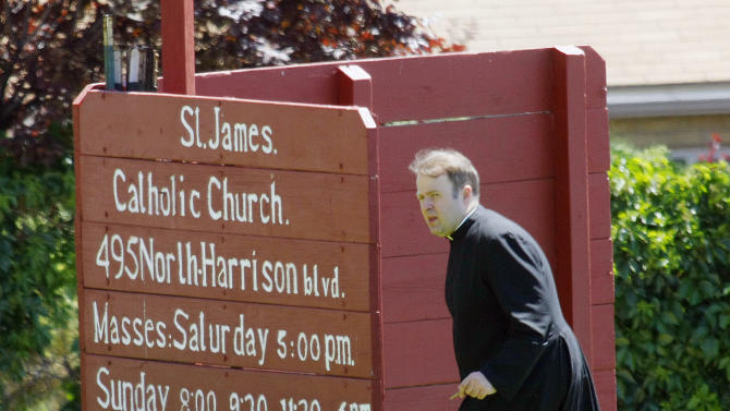 In this Sunday, June 16, 2013 photo, a clergyman walks up a small rise near the entrance of St. James Catholic Church in Ogden, Utah after police say Charles Richard Jennings Jr. walked in and shot his 65-year-old father-in-law, James Evans, in the head in front of a congregation of 300 people. Jennings was arrested on I-84 near Tremonton after the truck he stole ran out of gas. Evans is expected to survive. (AP Photo/The Deseret News, Scott G Winterton) SALT LAKE TRIBUNE OUT; MAGS OUT