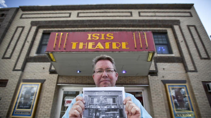 """In this photo from Sept. 4, 2012, Thom Reeves, owner of the Isis theatre, holds a photo showing the building's facade in 1932 during the showing of the movie """"The Kid from Spain"""", starring Eddie Cantor, in Crete, Neb. The Isis Theatre hasn't changed much since it opened 86 years ago, but as the movie industry phases out the traditional 35 mm film reels in favor of digital media, the Isis' owner must come up with $85,000 to buy new projection equipment, computers, a sound system and even a different screen. It is a huge financial burden for the small theatre. (AP Photo/Nati Harnik)"""