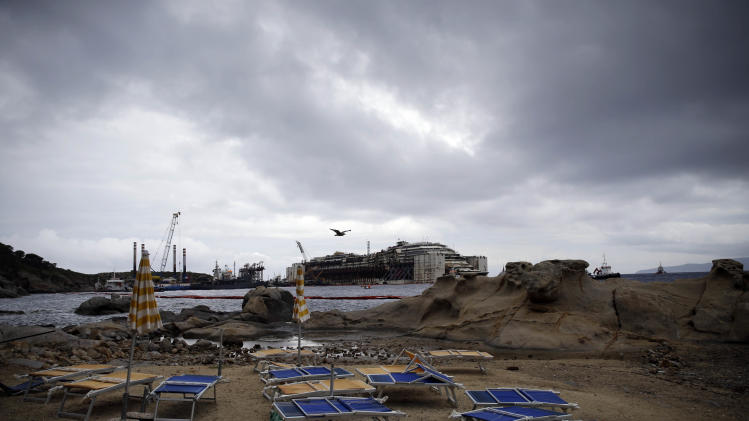 Empty sun beds and closed umbrellas are seen on a beach in front of the luxury cruise ship wreck Costa Concordia in the tiny Tuscan island of Isola del Giglio, Italy, early Tuesday, July 22, 2014. The towing of the wreck of the Costa Concordia to the Italian port of Genoa where it will scrapped has been postponed to Wednesday due to a minor technical problem in the positioning of the buoyancy sponsons. A convoy of 14 ships will escort the wreck in its last journey ending a 1.5 billion euros (2 billion US dollars) operation entirely funded by Costa Crociere. (AP Photo/Gregorio Borgia)