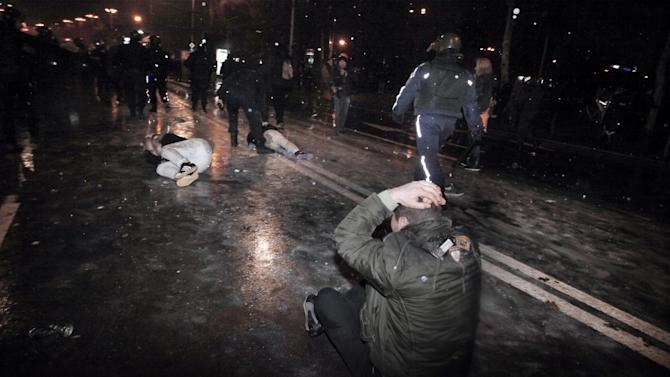 Protesters are detained by the riot police during a protest against high electricity prices in Sofia, on late Tuesday, Feb. 19, 2013.  Bulgaria's prime minister announced on Tuesday that the license held by a Czech company for power distribution in parts of the Balkan country will be revoked following protests against high electricity prices. (AP Photo/Valentina Petrova)