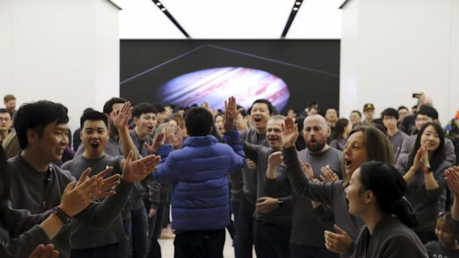 Staff members greet a customer entering a new Apple Store in Beijing
