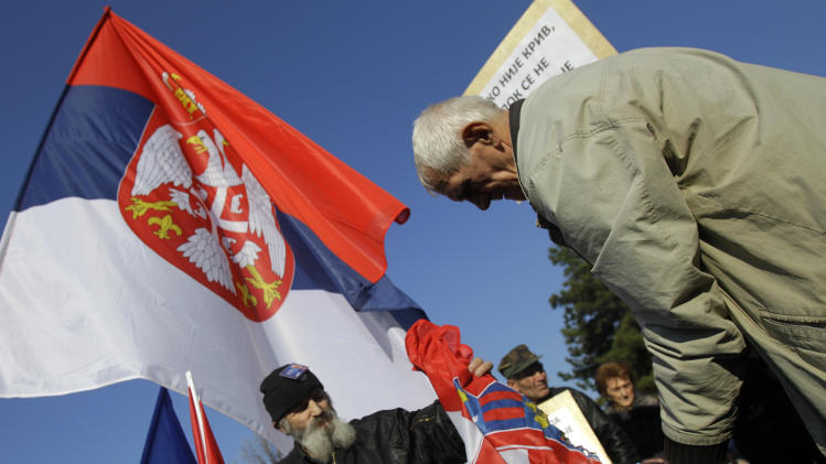 Protesters burn a Croatian flag during the protest in front of the presidency building in Belgrade, Serbia, Saturday, Nov. 17, 2012. A few hundred hardline Serbian nationalists  burned a Croatian flag, angry that a U.N. war crimes court has overturned the convictions of two Croatian generals for murdering and expelling Serbs in a 1995 offensive. Serbia is furious that the appeals judges at the Hague court on Friday freed generals Ante Gotovina and Mladen Markac, who previously had been sentenced to lengthy prison terms for crimes against Serbs. (AP Photo/Darko Vojinovic)