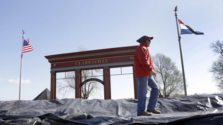 A member of the the Army Corps of Engineers walks atop a temporary levee constructed in an effort to hold back the swollen Mississippi River Saturday, April 20, 2013, in Clarksville, Mo. Communities along the Mississippi River and other rain-engorged waterways are waging feverish bids to hold back floodwaters that may soon approach record levels. (AP Photo/Jeff Roberson)