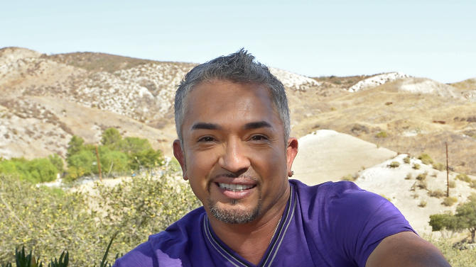 """In this Oct. 18, 2012 photo, Cesar Millan poses with his English Bull Dog George at his Dog Psychology Center, in Santa Clarita, Calif. Millan has a new television show, book, tour and documentary. """"Cesar Millan: The Real Story"""" airs on Nat Geo Wild on Nov. 25, 2012. It will also launch a global speaking tour. (AP Photo/Mark J. Terrill)"""