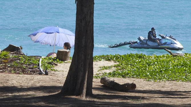 A police Jet Ski patrols a beach near where President Barack Obama and the first family are spending time at Bellows Air Force Station, Hawaii, Friday, Dec. 26, 2014, during the Obama family vacation. (AP Photo/Jacquelyn Martin)