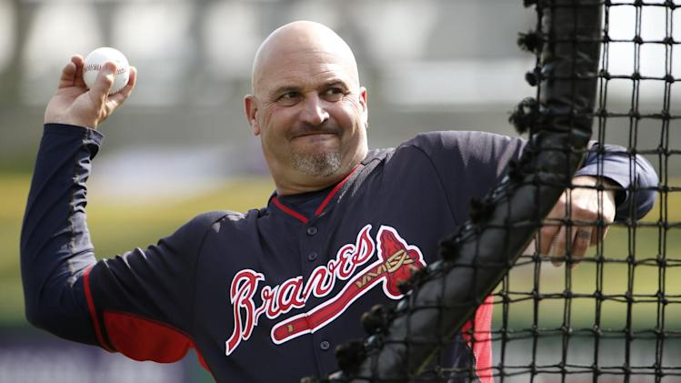 Atlanta Braves manager Fredi Gonzalez throws batting practice before a spring exhibition baseball game against the Philadelphia Phillies in Clearwater, Fla., Monday, March 10, 2014