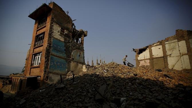 A man pushes cart filled with bricks, as he removes debris from collapsed houses, a month after the April 25 earthquake in Kathmandu