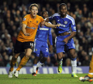 Chelsea's Didier Drogba, right, grapples with Wolverhampton Wanderers' Christophe Berra during their English Premier League soccer match at the Stamford Bridge Stadium, London, Saturday, Nov. 26, 2011. (AP Photo/Tom Hevezi)