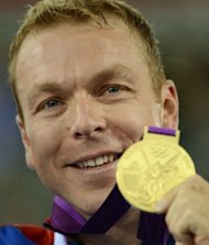 Great Britain's Chris Hoy celebrates with his gold medal on the podium during the victory ceremony for the Men's team sprint as part of the track cycling event of London 2012 Olympic games, in London