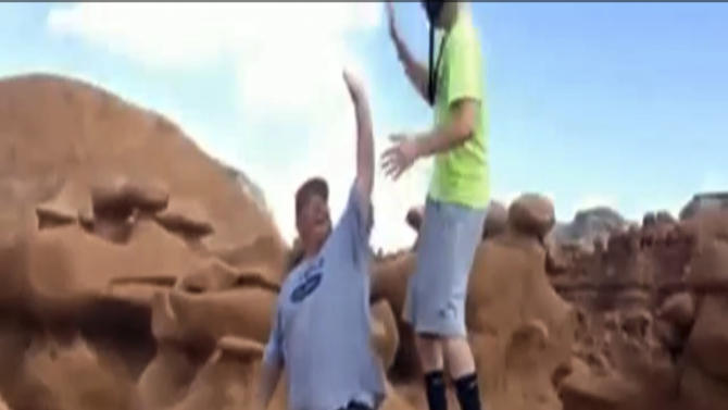 FILE - This file frame grab from a video taken by Dave Hall shows two men cheering after a Boy Scouts leader knocked over an ancient Utah desert rock formation at Goblin Valley State Park. Prosecutors have filed charges Friday Jan. 31, 2014, against two former Boy Scout leaders accused of toppling ancient rock formations at Utah's Goblin Valley State Park. State Parks officials say Glenn Taylor was charged with criminal mischief. David Hall was charged with aiding criminal mischief, another felony. (AP Photo/Dave Hall, File)